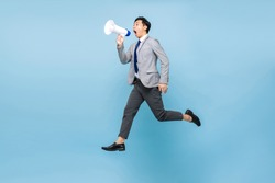 Young Asian businessman jumping and shouting on megaphone isolated on light blue color background