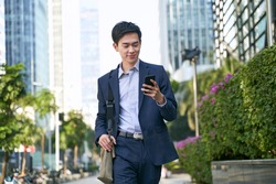 young asian businessman looking at messages on cellphone while walking in the street in downtown of modern city