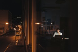 Young Asian businessman sitting at his desk working on a laptop late at night behind office building windows in the city at night