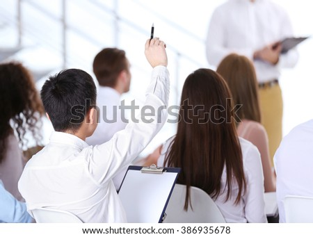Young Asian businessman sitting back and raising hand at the office meeting - Shutterstock ID 386935678
