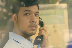 Young Asian businessman using the payphone outdoors
