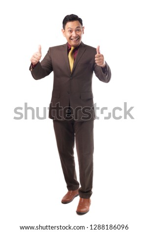Young Asian businessman wearing brown formal suit shows thumb up gesture, smiling happy satisfied OK gesture, full body portrait isolated on white