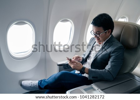 Young asian businessman with suit sitting in business first class seat inside airplane via using smartphone with happiness