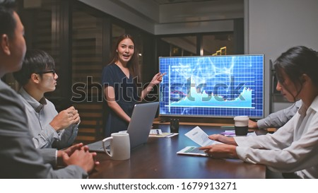 Young Asian businesswoman lead group of business financial team in strategic meeting presentation, work late night in office. Marketing strategy analysis, stock market trading, or corporate teamwork