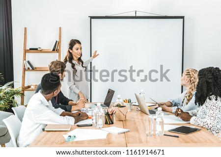 young asian businesswoman pointing at projection screen while making presentation in office