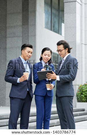 Young Asian businesswoman typing on tablet pc with two businessmen standing near by her and looking at her online work outdoors stock photo