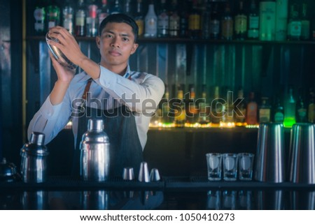 Young Asian casting bartenders are shaking the ingredients of the cocktail is the bar counter area behind the scenes of him filled with drinks that contain alcohol with copy space #1050410273