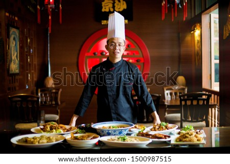 Young Asian chef displaying his special traditional gourmet on the table in an Oriental restaurant setting. Dinner for family. Chinese New Year ambiance. Kitchen work. Professional cook.
