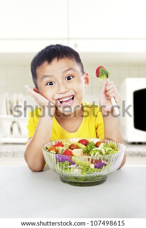 Young asian child with salad smiling in the kitchen. shot in the kitchen room