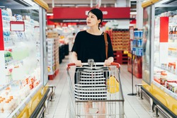 Young asian chinese charming pregnant woman pushing shopping cart with grocery products shelves on side. beautiful future motherhood buying food with trolley in store. elegant parent in supermarket