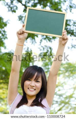 Young Asian college girl arms up holding a blackboard outdoor, green park