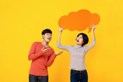 Young Asian college student friends in casual clothes with speech bubble on colorful yellow studio background