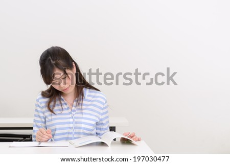 Young Asian college student studying in class room.