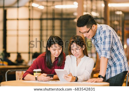 Young Asian college students or coworkers using digital tablet and smartphone together at coffee shop, diverse group. Casual business, freelance work at cafe, social meeting, or education concept #683542831