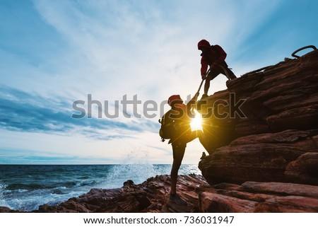 young asian couple climbing up...