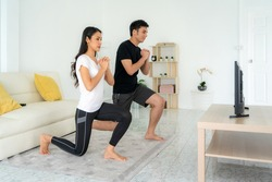 Young Asian couple doing squats training together and looking TV at home, man and woman working out together standing in living room, fit pair performing fitness exercise with partner.