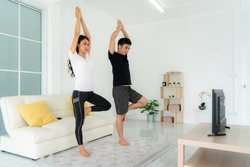 Young Asian couple doing yoga practice together and looking TV at home, man and woman working out together standing in living room, fit pair performing fitness exercise with partner.