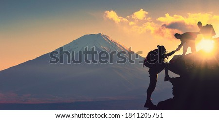 Young asian couple hikers climbing up on the peak of mountain near mountain fuji. People helping each other hike up a mountain at sunrise. Giving a helping hand. Climbing. Helps and team work