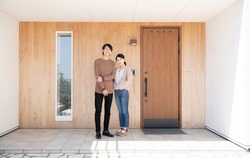 Young asian couple in front of the house.