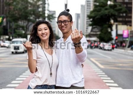 Young Asian Couple Inviting Someone to Come #1016922667