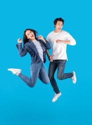 Young Asian couple man and woman jumping with happy and fun over blue background
