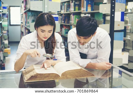 Young Asian Couple of students at the library reading a book together. Education concept. #701869864