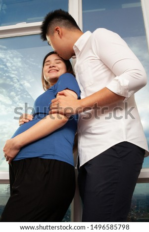 Young Asian couple showing affectionate waiting for the baby born