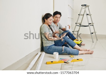 Young Asian couple sitting at wall, drinking coffee and discussing plan of apartment renovation on tablet computer