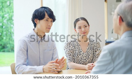 Young Asian couple talking with a senior man. Stock fotó ©