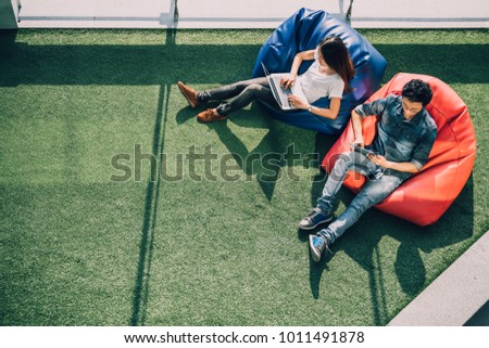 Young Asian couple using laptop notebook and digital tablet together in modern public park, sit on bean bag, top view with copy space on grass. Information technology gadget or casual business concept Stock photo ©