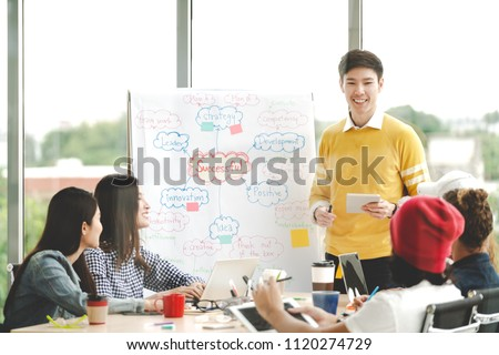 Young asian creative businessman standing and making presentation at modern office happy talking and brainstorming with teamwork behind transparent glass wall. Casual people business meeting concept.