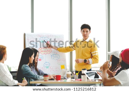 Young asian creative businessman standing and making presentation at modern office happy talking and brainstorming with team by pointing ideas on flipchart. Casual people business meeting concept.
