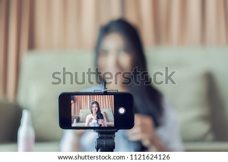 Young Asian cute artist woman beauty vlogger or blogger doing a cosmetic makeup tutorial vlog with brushes looking camera smartphone,recording viral clip share on social media live streaming Internet