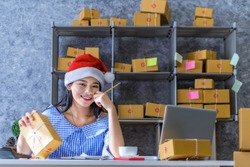 Young Asian doing their own business on shopping online at home office packaging on background is a popular business.  online shopping SME entrepreneur or freelance working concept.