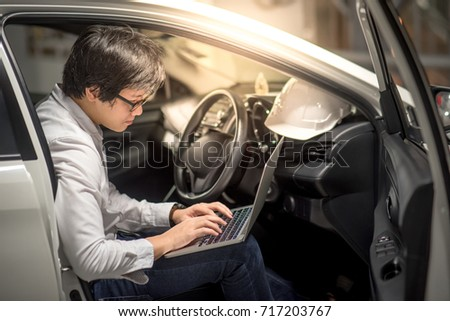 Young Asian Engineer or Architect working with laptop computer while sitting in his car. Mechanical engineering and building construction concepts