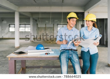 Young Asian engineers couple working together on building blueprint at construction site or factory. Civil engineering, industrial business partner, or home renovation service concept. With copy space #788664025