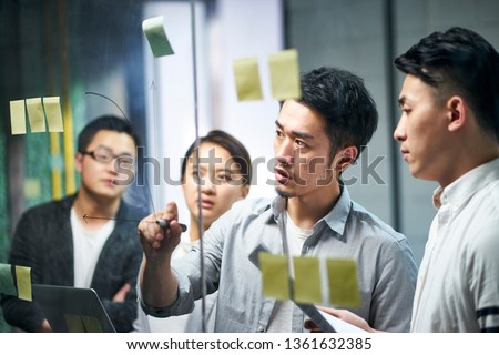 young asian entrepreneur of small company drawing a diagram on glass during team workshop in office discussing and formulating business strategies.