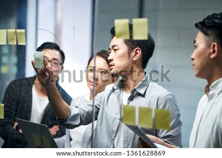 young asian entrepreneur of small company putting a adhesive note on glass in office during team meeting formulating business strategies.