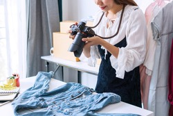 Young Asian entrepreneur using a camera take a photo of product for upload to website online shop. Online selling, e-commerce, business and technology concept.