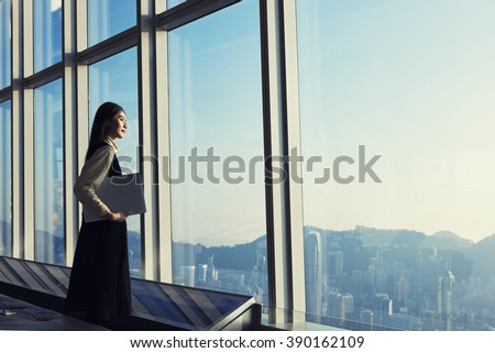 Young Asian executive holding laptop computer, while is standing in office interior and looking out of big window with city view. Female manager with net-book in hand ponder about new business project