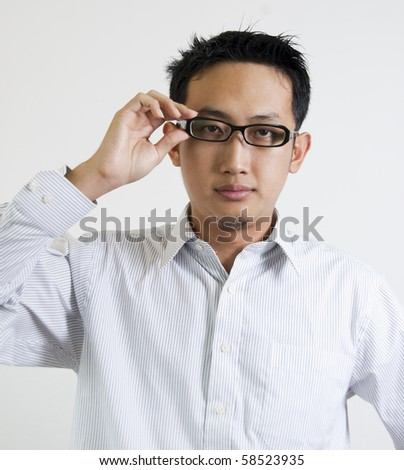 Young Asian executive is adjusting his spectacles