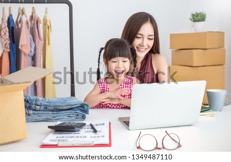 Young asian family woman and girl packing cardboard box in the office SME business, family mother daughter moving house and small business, SME work from home business, cyberspace together concept