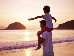 young asian father carrying son on shoulder on beach at sunrise.