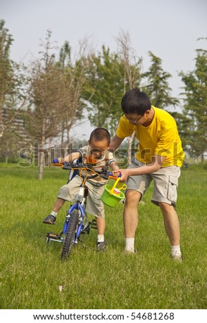 Young asian father is teaching his son riding bicycle - stock photo