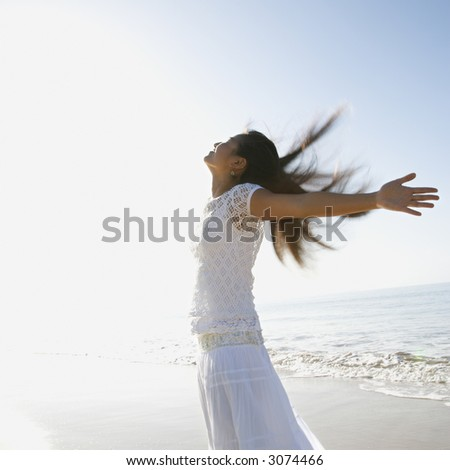 Young Asian female at beach throwing her arms back behind her.