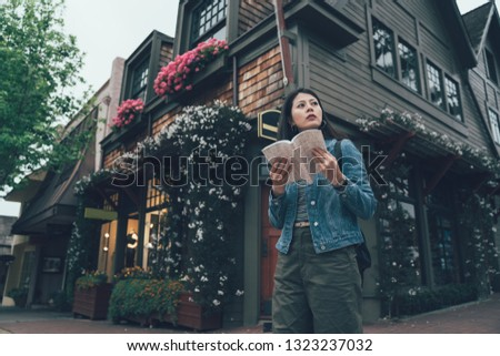 young asian female backpacker holding guide book standing by american style house with flower on corner in carmel by the sea california. chinese lady tourist with map searching information trip usa.