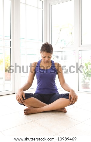 Young Asian female doing neck stretching exercise to release build up tension.