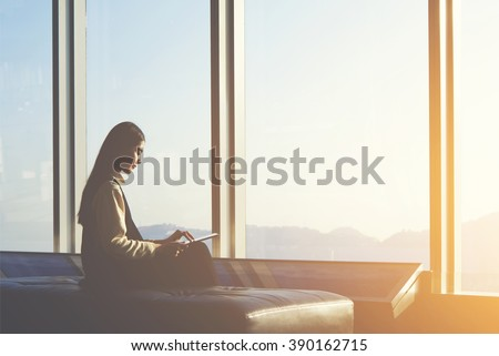 Young Asian female is watching news on digital tablet, while is sitting in airport interior against window with copy space area.Attractive Chinese woman is using portable computer and waiting her fly