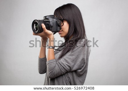 Young asian female photographing with SLR on an isolated background. #526972408
