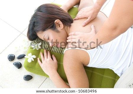 Young Asian female receiving back massage in spa as part of beauty and healthcare modern lifestyle.